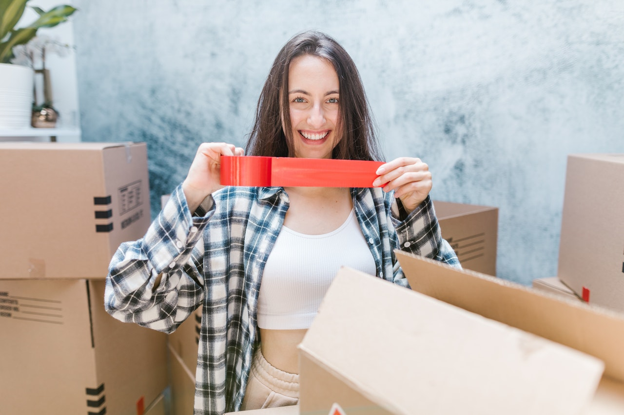 girl surrounded by boxes holding a duct tape