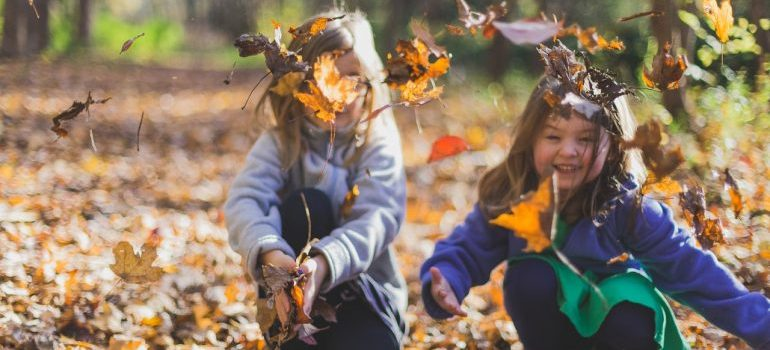 Kids playing with dry leaves.
